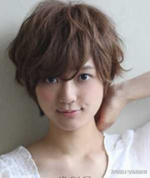 很适合小圆脸女生的一款平刘海的蓬松短发烫发发型,将头发染成了棕色