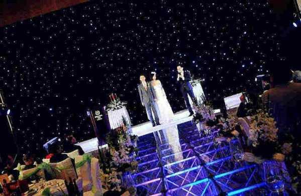 星空幕布婚礼现场背景布置图片欣赏 韩式浪漫星空系主题婚礼舞台灯光布置图片   时尚星空幕布婚礼现场背景布置很不错,开阔大方的格调在这里演绎了出来,星空样式的背景墙很精美,闪烁明朗的效果展现,中央玻璃T台很精美,内置的灯池在这里萦绕,再加上新鲜的花束环绕两侧,带来了芬芳的花香,生机与活力也在这里散发,从这里走过,感受幸福的时刻。